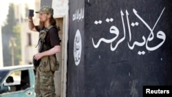 A militant Islamist fighter uses a mobile to film his fellow fighters taking part in a military parade along the streets of Syria's northern Raqqa province, June 30, 2014.