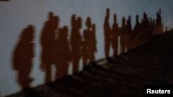 Familias migrantes solicitantes de asilo proyectan sombras en una pared mientras forman una cola para ser procesadas por la Patrulla Fronteriza de EE. UU. después de cruzar el Río Bravo hacia los Estados Unidos desde México en Texas, el 12 de agosto.