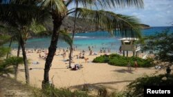 FILE - People enjoy a beach day at Hanauma Bay, on the east side of Oahu, Hawaii.