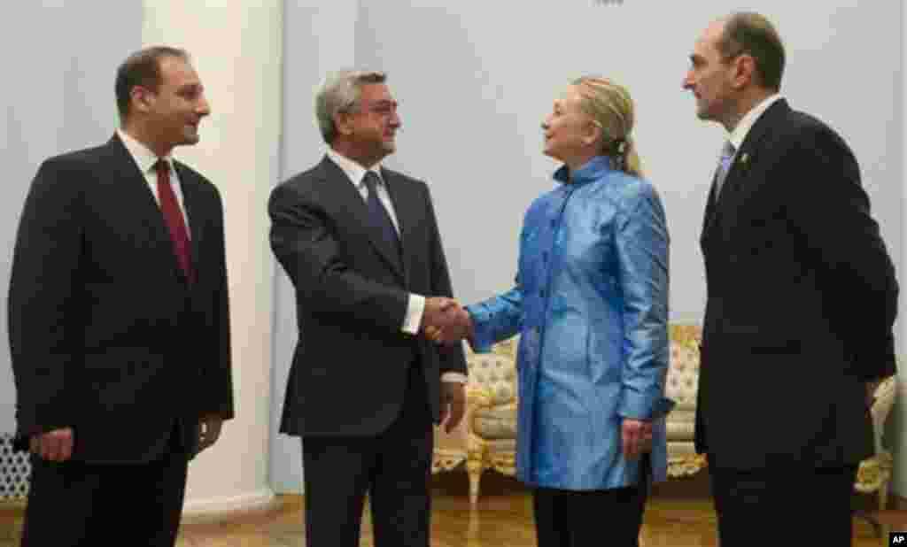 Armenian President Serzh Sarkisian, 2nd left, shakes hands with US Secretary of State Hillary Clinton Monday June 4, 2012 alongside translators before meetings at the presidential palace in Yerevan. (AP Photo/Saul Loeb, Pool)