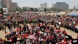 Opozan prezidan dechouke Mohamed Morsi ap fè drapo nasyonnal la flote, tandiske yo gen nan men yo foto Lt. Gen. Abdel-Fattah el-Sissi, sou plas Tahrir la, nan vil Lekèr (Vandredi 5 jiyè 2013).