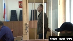 FILE - Eston Kohver of Estonia stands behind bars in Pskov, Russia, Sept. 17, 2014.