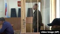 FILE - Eston Kohver of Estonia stands behind bars in Pskov, Russia, Sept. 17, 2014.
