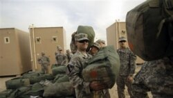 U.S. Army soldiers load trucks as they begin their journey home to their base in Texas