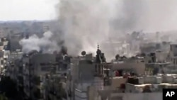 This image made from amateur video released by Shaam News Network and accessed Friday, June 8, 2012, purports to show explosions in the Khaldiyeh area of Homs, Syria. Syrian troops on Friday heavily shelled a rebel-held neighborhood in the flashpoint cent