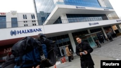 A TV correspondent reports in front of Halkbank headquarters in Atasehir, in the Asian part of Istanbul, Dec. 17, 2013.