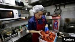 北京一家餐馆厨工用进口美国龙虾准备午餐(路透社2018年7月5日)
