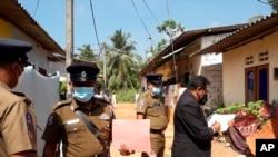 Hakim Sri Lanka Wasantha Ramanayake (kanan) dan polisi memeriksa suasana di luar sebuah rumah, tempat seorang gadis berusia sembilan tahun tewas di Delgoda, Sri Lanka, Minggu, 28 Februari 2021.