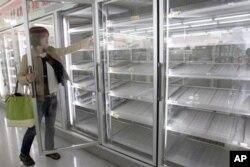 一女士从东京某便利店几乎空掉的货柜里拿出一瓶果汁