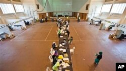 Electoral workers engage in the vote tally verification process at the National Tallying Center