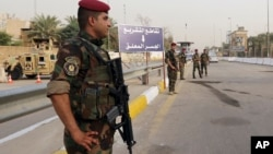 Iraqi security forces stand guard as they check motorists entering the heavily fortified Green Zone in Baghdad, Iraq, Oct. 5, 2015.