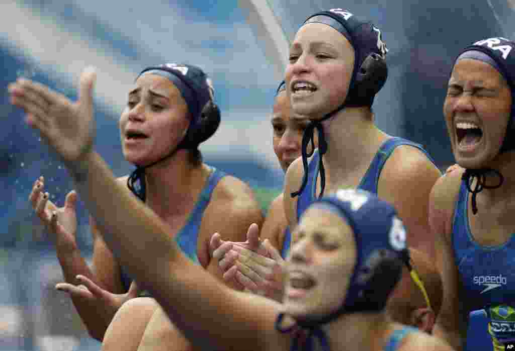 Brazil players cheer their teammates during a preliminary women's water polo match against Russia at the Summer Olympics in Rio de Janeiro, Brazil.