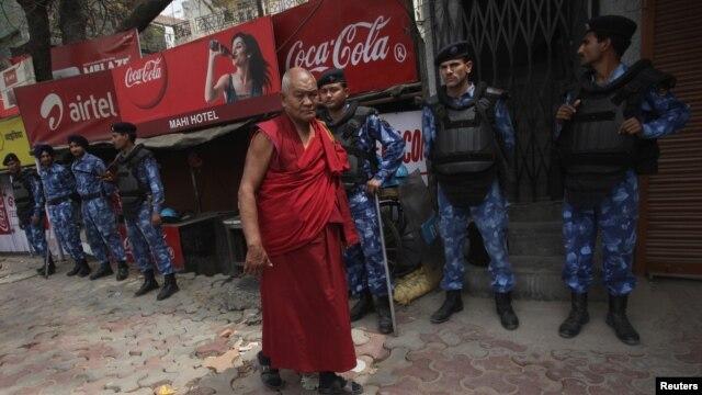 Tibetan exile walks past Rapid Action Force personnel at Majnu Ka Tila, a Tibetan refugee camp, New Delhi, March 27, 2012.