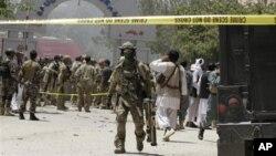 Seorang tentara NATO (tengah) terlihat di depan lokasi hotel Spozhmai di Danau Qargha, utara Kabul, Afghanistan (22/6).