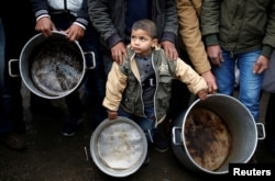 A Palestinian boy holds cooking pots during a protest against aid cuts, outside United Nations' offices in Gaza City January 24, 2018.