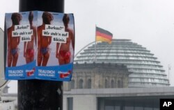 "FILE - An election poster of the nationalist Alternative for Germany, AfD, reading ""Burka? We prefer bikinis"" hangs on a lamp post in front of the Parliament building Berlin, Germany, Sept. 24, 2017. Some Germans fear that a new election would only strengthen the hand of the far-right."