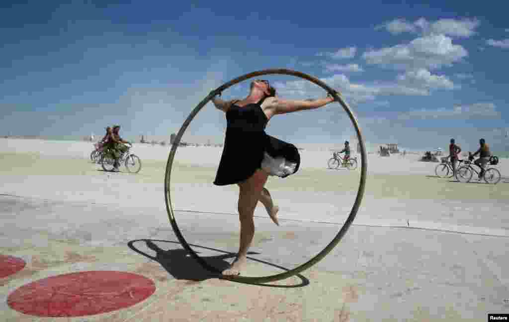 នាង Kylie Webb អ្នកចូលរួមក្នុងទិវា Burning Man កំពុងបង្វិលខ្លួននៅក្នុងកងដែកមួយនៅលើទីលានរាំឌីស្កូនៅពេលដែលមនុស្សជាង៧០.០០០នាក់មកពីទូទាំងពិភពលោកបានមកប្រមូលផ្តុំគ្នាក្នុងថ្ងៃទី១នៃពិធីបុណ្យសិល្បៈនិងតន្រ្តី Burning Man ប្រចាំឆ្នាំនៅកណ្តាលវាលខ្សាច់ Black Rock រដ្ឋ Nevada កាលពីថ្ងៃទី២៨ សីហា ២០១៧។