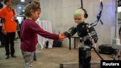 Seorang anak perempuan memberikan bola kepada sebuah robot dalam sebuah Pameran Robot Manusia di Madrid, 19/11/2014.