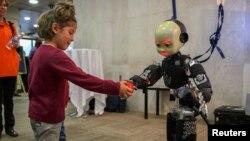 Una niña entrega una pelota a un robot humanizado en una conferencia en Madrid.