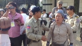 Police ask an activist to stand near the U.S. embassy and wait for officials to receive her petition that calls for U.S. intervention to release union leaders and workers arrested in early January, Phnom Penh, Jan. 21, 2014. (Heng Reaksmey/VOA)