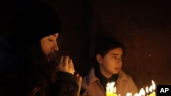 A woman prays after evening service. Christmas in the Armenian tradition is a purely religious affair.