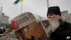 A man reads a newspaper with a picture of Russian President Vladimir Putin on the front page during a pro-European Union rally in Independence Square in Kiev, Ukraine, Thursday, Dec. 19, 2013.