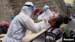 在新疆烏魯木齊一名穿防護服的醫務工作者對居民進行核酸檢測。 (2020年7月19日)