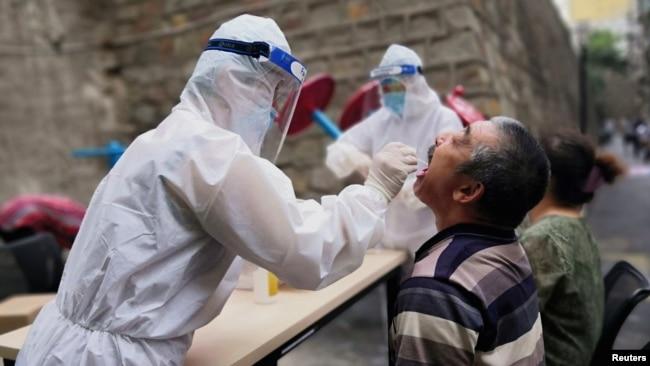 中国新疆乌鲁木齐一名医护人员正在对居民进行核酸检测。