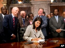 FILE - Then-South Carolina Gov. Nikki Haley signs a bill into law as former South Carolina governors and officials look on, July 9, 2015, at the Statehouse in Columbia, S.C. The law enabled the removal of the Confederate flag from the Statehouse grounds more than 50 years after the rebel banner was raised to protest the civil rights movement.