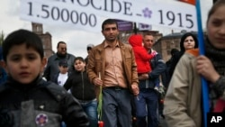 "FILE - Armenians carry a placard with a sign reading ""1915"" and ""1500000"", the year and alleged numbers of victims of mass killings of Armenians by Ottoman Turks on a street in Yerevan, Armenia, April 24, 2015. Turkey denies the killings were genocide."