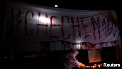 FILE - Activists from the group Chok3 paint a banner with their own blood during a protest discrimination and violence against the gay community in Chechnya and other regions of Russia, outside the Russian Embassy in Mexico City, Mexico, April 20, 2017.