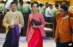 FILE - Myanmar opposition leader Aung San Suu Kyi walks along with other lawmakers of her National League for Democracy party. The NLD won an overwhelming majority of seats in both houses of parliament in last November's election.