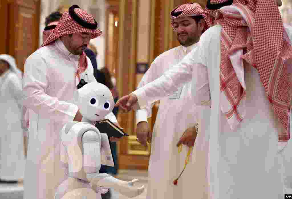 Delegates chat near a robot during the Future Investment Initiative forum at the King Abdulaziz Conference Centre in Saudi Arabia's capital Riyadh.