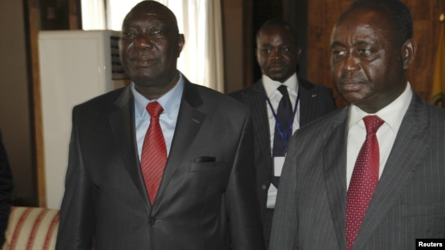 Michel Am-Nondokro Djotodia (L), leader of Central African Republic's (CAR) Seleka rebel alliance, stands beside CAR's President Francois Bozize (R) during peace talks between the government and the opposition rebels in Libreville, Gabon, January 11, 2013.