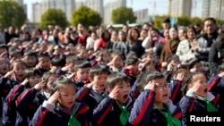 2018年2月23日,中國上海一所小學新學期第一天舉行的升旗儀式上,學生致敬。