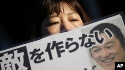A Japanese woman reads a newspaper article about Kenji Goto.