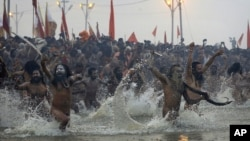 Indian Hindu holy men run naked into the water at Sangam, the confluence of the rivers Ganges, Yamuna and mythical Saraswati, during the royal bath at the start of the Kumbh Mela in Allahabad, India, Janaury 14, 2013.