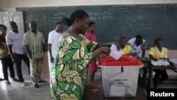 Une femme met son bulletin dans l'urne dans un bureau de vote de Cotonou, pour la présidentielle béninoise, le 6 mars 2016. (REUTERS/Akintunde Akinleye - RTS9I4A)