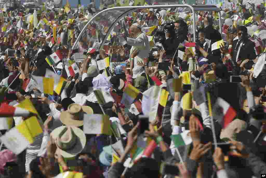Catholic faithful cheer as Pope Francis drives by in his popemobile in Ecatepec, Mexico, Feb. 14, 2016.