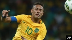 Le Brésilien Neymar, à gauche, dégage une balle de la tête lors d'un match contre le Danemark au stade de Fonte Nova à Salvador, Brésil. 10 août 2016.