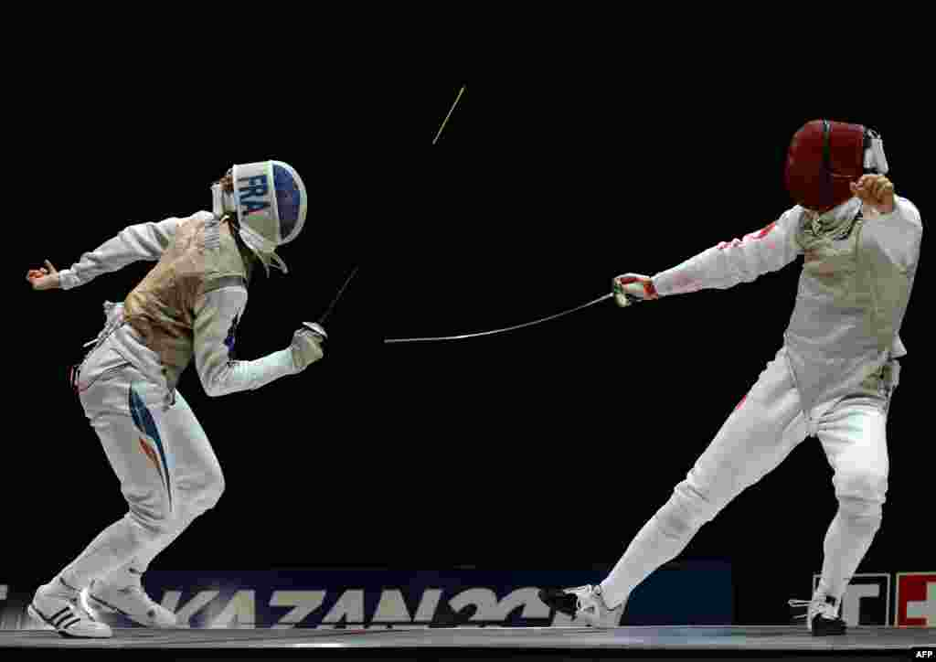 Julien Mertine of France (L) competes against Jianfei Ma of China during the men's team foil final at the 2014 World Fencing Championships in Kazan, Russia, July 22, 2014.