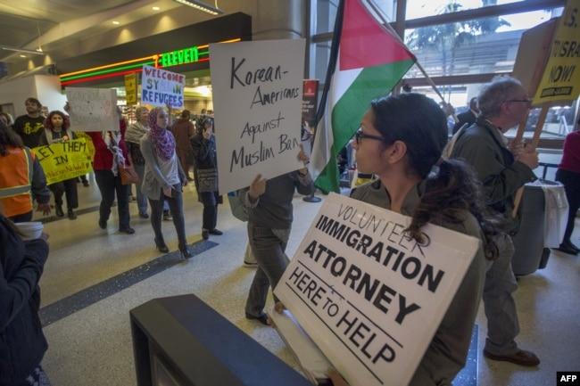Manifestantes en el aeropuerto de Seattle pasan frente a una abogada voluntaria de inmigración, mientras apoyan el fallo de un juez federal en la ciudad, que suspendió temporalmente una prohibición temporal de viajes ordenada por el presidente Donald Trump contra ciudadanos de siete países de mayoría musulmana y refugiados.