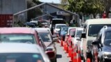 FILE - Members of the public wait in cars at a drive-through coronavirus disease (COVID-19) vaccination clinic during a single-day vaccination drive, in Auckland, New Zealand, Oct. 16, 2021.