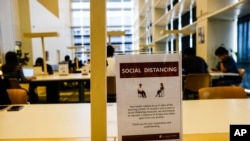 A sign about social distancing is placed on a table at the National Library in Singapore, March 16, 2020.