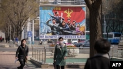 FILE - People wearing face masks walk before a propaganda poster displayed on a street in Pyongyang, April 9, 2020.