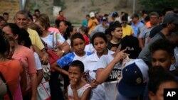 Migrantes de varios países latinoamericanos hacen fila para recibir alimentos de voluntarios estadounidenses al pie del puente que cruza a Brownsville, Texas, en Matamoros, México. Cientos esperan por meses en fila para solicitar asilo en EE.UU. Foto de junio 26 de 2019.