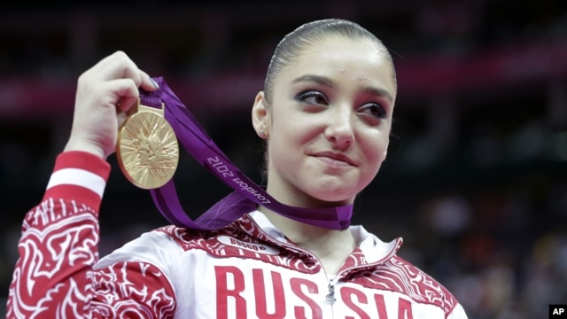 Russian gymnast Aliya Mustafina displays the gold medal for her performance on the uneven bars during the artistic gymnastics women's apparatus finals at the 2012 Summer Olympics, Aug. 6, 2012, in London.