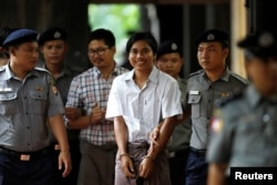 FILE - Police escort detained Reuters journalists Kyaw Soe Oo and Wa Lone as they arrive before a court hearing in Yangon, Myanmar, Aug. 20, 2018.