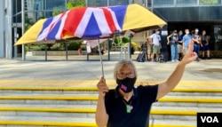 社运人士王婆婆9月15日在湾仔区域法院外撑起贴上英国国旗的黄伞,声援六四未经批准集结案,12名认罪的被告(美国之音/汤惠芸)