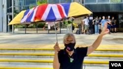 社運人士王婆婆9月15日在灣仔區域法院外撐起貼上英國國旗的黃傘,聲援六四未經批准集結案,12名認罪的被告(美國之音湯惠芸)